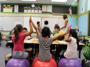students on balloon chairs with hands in air