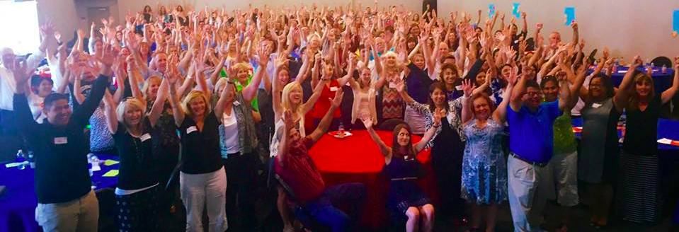 Teacher Summit group picture with hands raised